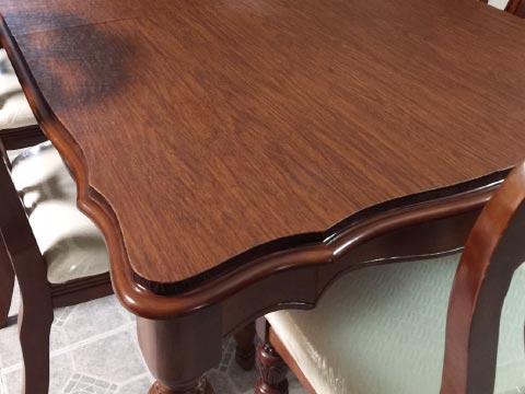 Table protector with custom shaped edge in cherry woodgrain