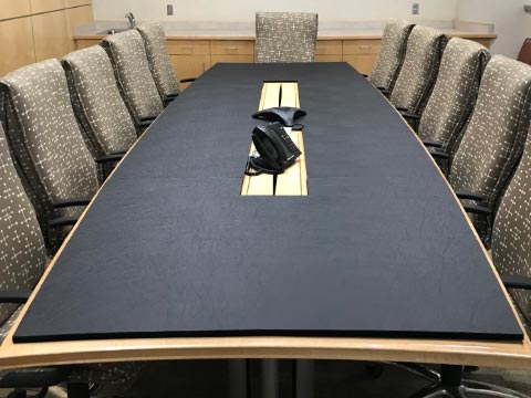 Conference room table pad with cutouts for phones and cables