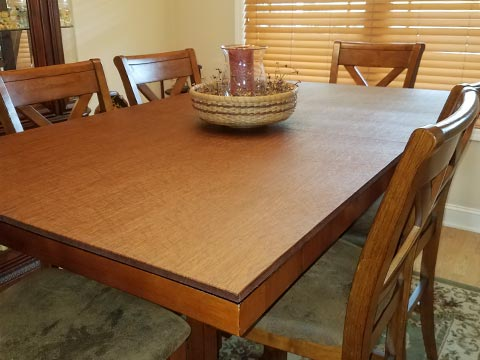 Dining room table pad protecting table from candle centerpiece, in medium cherry woodgrain
