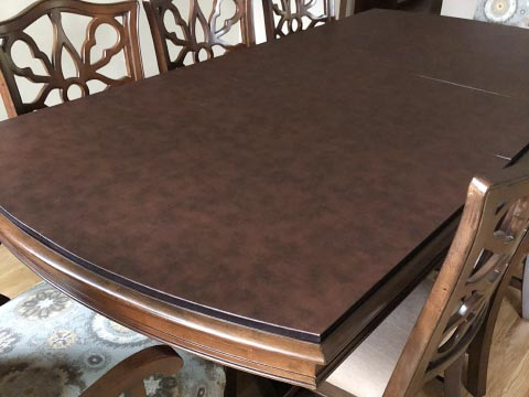 Leather-look dining table protector pad with curved ends and straight sides